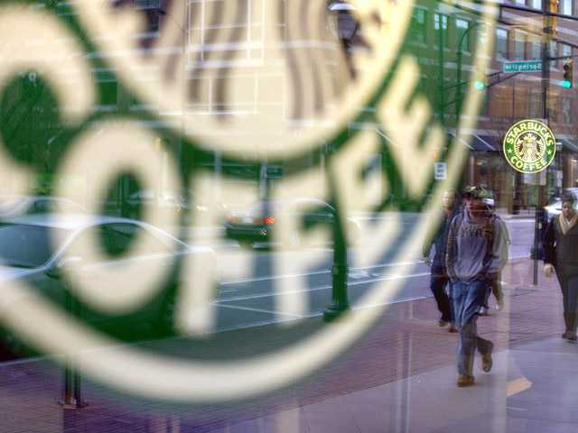 In this Jan. 26, 2011, file photo, pedestrians are reflected outside a Starbucks store in Atlanta.