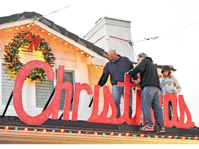 From left, Mike Halverson, Tim Archer and Emily Halverson attach a sign to the roof of the Halverson home on Wakefield Court in Saugus.