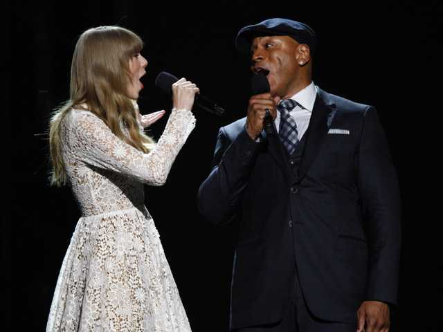 Hosts Taylor Swift, left, and LL Cool J sing onstage at the Grammy Nominations Concert Live! at Bridgestone Arena on Wednesday in Nashville, Tenn.