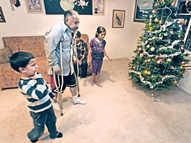 Nephew Kevin Herrera, 6, and his sister Elizabeth,  9, assist uncle Francisco Lara as he walks with crutches at his sister's home in Canyon Country.