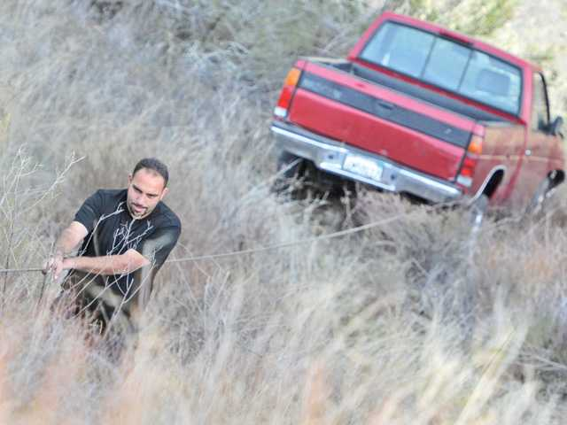 William Haddad of Freeway Towing climbs up a cable attached to a Nissan truck on Wednesday that went off the side at Rush Canyon Road near Sierra Highway in Acton.