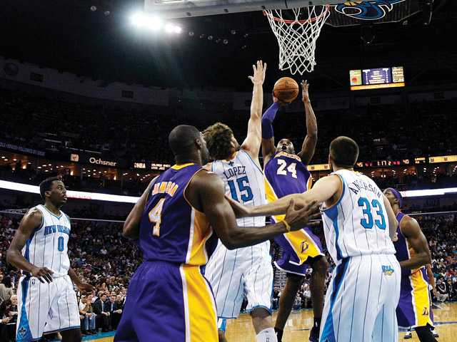 Los Angeles Lakers guard Kobe Bryant (24) shoots over New Orleans Hornets center Robin Lopez (15) in New Orleans on Wednesday. With the basket, Bryant became the youngest player in NBA history to break 30,000 points.