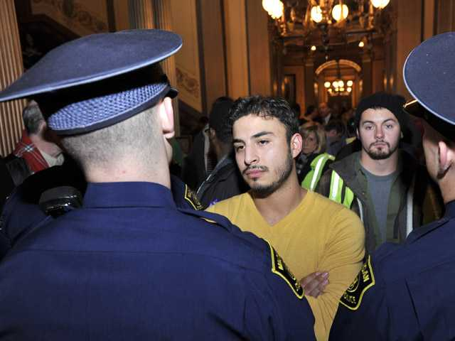 State Police block protesters outside the Senate chamber at the State Capitol Building in downtown Lansing, Mich.