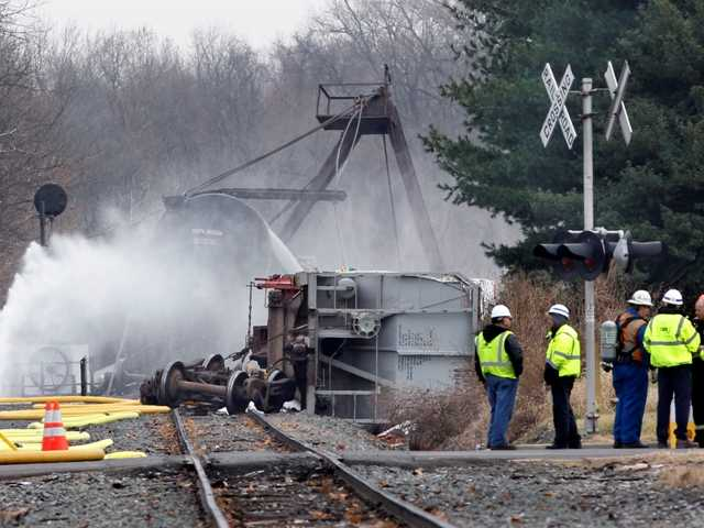 Crews spray water on derailed freight train tank cars in Paulsboro, N.J., Dec. 1, 2012, after seven cars of an 84-car freight train with two locomotives derailed causing a hazardous chemical to spew into the air.