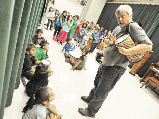 Dennis Poore demonstrates a drum for first graders at Fair Oaks Ranch Community School in Canyon Country on Monday.
