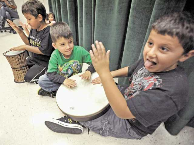 From left, Musa Rahman, Adam Almanzan and Zachariah Garabet try out drums during a music class at Fair Oaks Ranch Community School in Canyon Country on Monday.