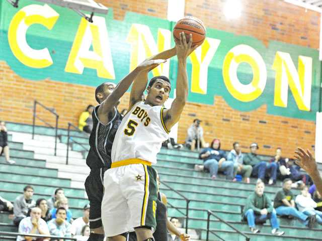 St. Genevieve's Mark Chin, left, tries to reach in for a rebound caught by Canyon's Dean Hendrix-Davis, right, on Thursday night at Canyon. The Cowboys won 67-57.