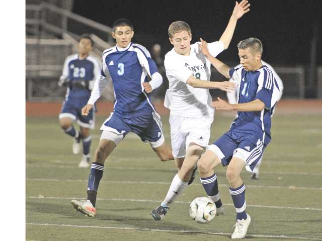 Canyon's Chad Ybarra (18) takes the ball down to the goal against Quartz Hill defenders Jose Luna (3) and Chance Carol (11) at Canyon High on Thursday. The game ended in a 3-3 draw.