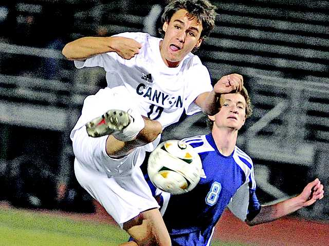Canyon's Timothy Wagner (12) takes a pass near the goal against Quartz Hill defender Koty Thomas (8) at Canyon on Thursday.