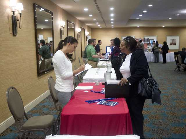 A person fills out an application at the Fort Lauderdale Career Fair, in Dania Beach, Fla., on Nov. 30.