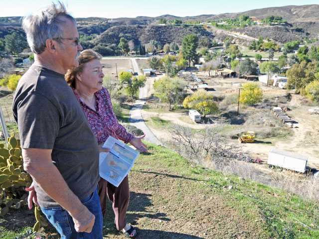 Larry and Dwanna Lousberg talk Friday outside their home atop a hill on Bouquet Canyon Road.