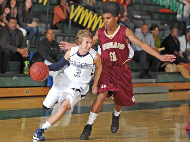 Saugus guard Nick O'Linn (3) drives to the basket on Highland's Tyree Cage on Friday at Canyon High during the Canyon Classic tournament.