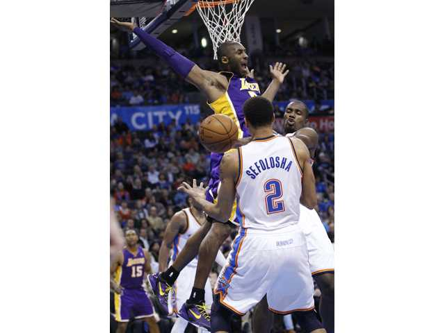 Los Angeles Lakers guard Kobe Bryant (24) loses control of the ball between Oklahoma City Thunder guard Thabo Sefolosha (2) and forward Serge Ibaka, right, in Oklahoma City on Friday.