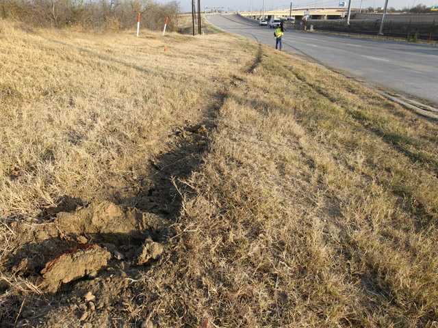 Tire ruts are seen with skid marks at the site of an accident involving Dallas Cowboys player Josh Brent as a news cameraman, rear, films the area, Saturday in Irving, Texas.
