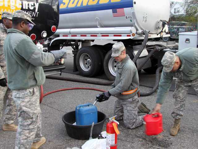 In this Nov. 3 photo, Staff Sgt. Nathan Roczen fills a gas canister for a member of the public who had waited in line for three hours for free gas in  Staten Island .