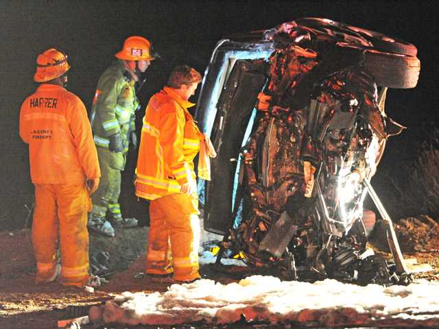 Firefighters inspect the remains of an overturned car on San Francisquito Road north of Stator Lane in the Angeles National Forest on Friday night. (Jonathan Pobre/The Signal)