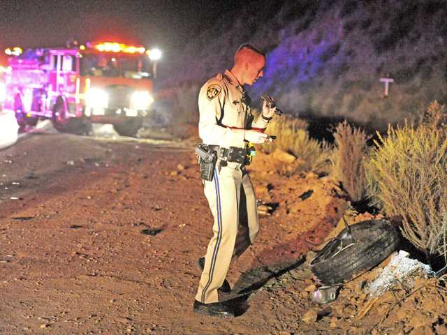 A California Highway Patrol officer investigates the scene of a two-car collision on San Francisquito Canyon Road in the Angeles National Forest on Friday night. (Jonathan Pobre/The Signal)