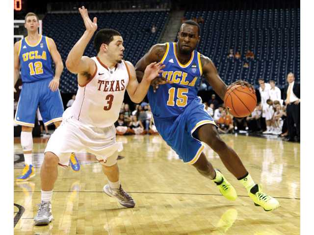 UCLA's Shabazz Muhammad (15) drives toward the basket as Texas' Javan Felix (3) defends at Reliant Stadium Saturday in Houston.