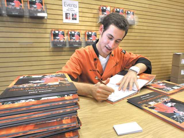 "Jake Tanner, 18, of Valencia and a freshman at Loyola Marymount University, autographs his cookbook ""Stick it in Your Pie Hole"" at a recent book signing at Barnes & Noble in Valencia."