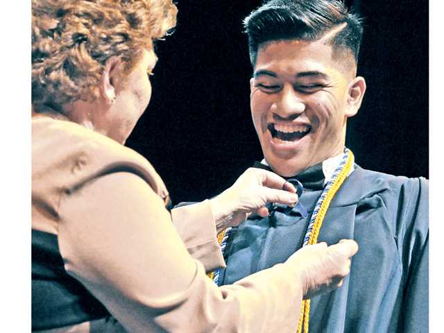 Nursing instructor Lori Brown left, pins graduating registered nurse Mike Malig on stage during the pinning ceremony.