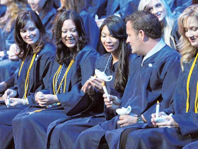 Graduating registered nurses light their candles on stage during the pledge and candle lighting ceremony.