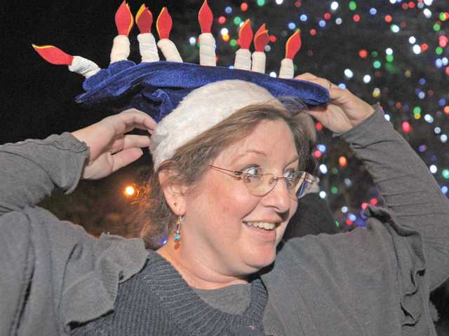 Stevenson Ranch resident B.J. Kaufman puts on her menorah hat as she attends the menorah lighting.