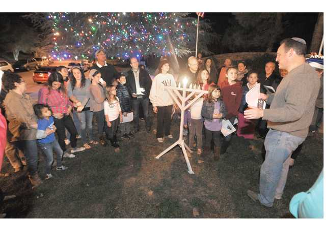 Rabbi Mark Blazer, right, leads the attendees during the menorah lighting gathering attended by some 35 people on Stevenson Ranch Parkway in Stevenson Ranch on Saturday.
