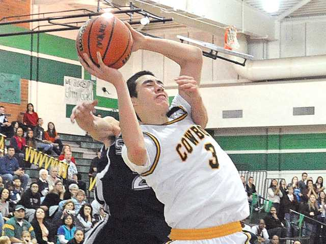 Canyon's Ben Taufahema (3) is fouled from behind by Saugus defender Jeff Ashburn on Saturday in the championship game of the Canyon Classic tournament at Canyon High School. Canyon won 43-42.