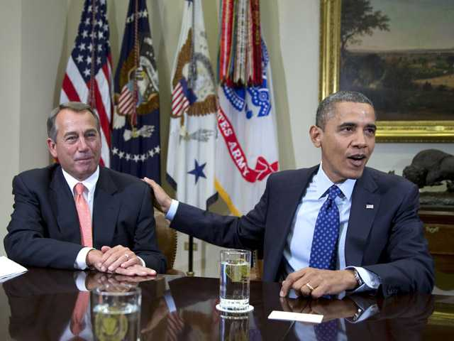 President Barack Obama acknowledges House Speaker John Boehner of Ohio while speaking to reporters at the White House in Washington.