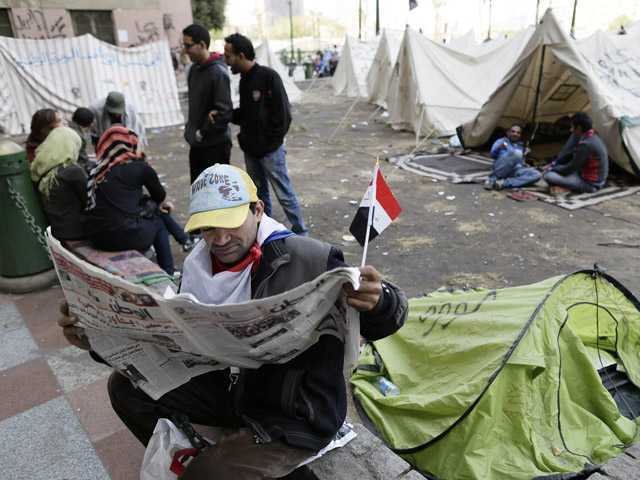An Egyptian protester reads the newspaper as other sit next to their tents in Tahrir Square in Cairo, Egypt, Sunday.