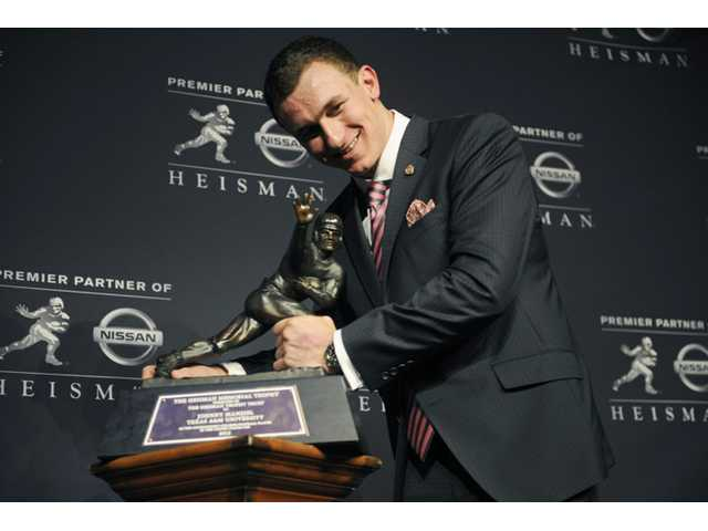 Texas A&M quarterback Johnny Manziel poses with the Heisman Trophy after becoming the first freshman to win the award on Saturday in New York.