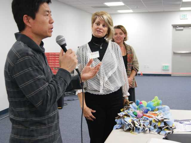 Santa Clarita Chinese School Principal Jinghong Li, left, introduces Mending Kids international representatives Naomi Carmona-Morshead, center, and Isabelle Fox. The school's students wrote 26 letters to orphaned children in China awaiting surgery.