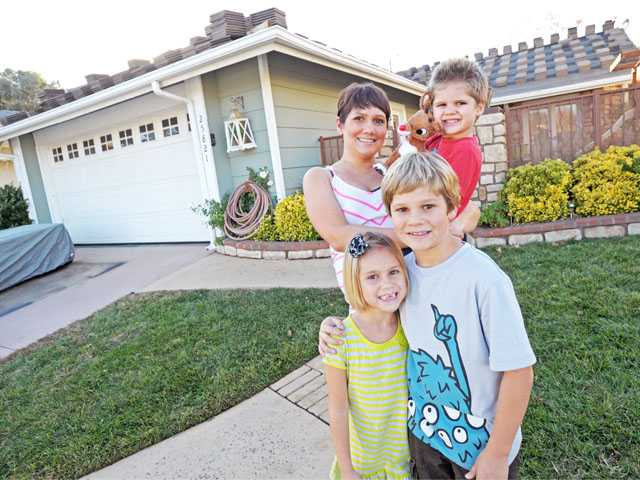 Jennifer Hill poses with her children, Bailey, 3, Emma (front left), 6, and Jayden, 8, in front of their Valencia home Monday. Not pictured is her husband, Kirk Hill. Signal Photo by Jonathan Pobre