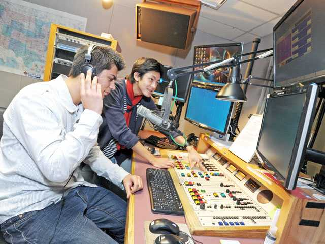 Saugus High School sophomore Andrew Whisler, left, and senior Cameron Quon try their hand at equipment in a radio studio on Thursday.