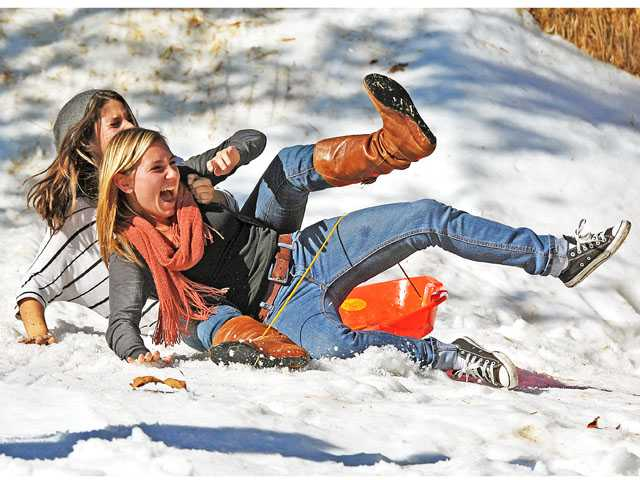 "Ashley Manley, front, and Nini Mansour take a spill as they slide down a hill of snow during Saugus High School's ""snow day"" on Monday. For a donation of food or money to the Santa Clarita Valley Food Pantry, students enjoyed activities in 30 tons of snow brought in by Newhall Ice Company, said ASB executive ambassador Tanner Diaz."