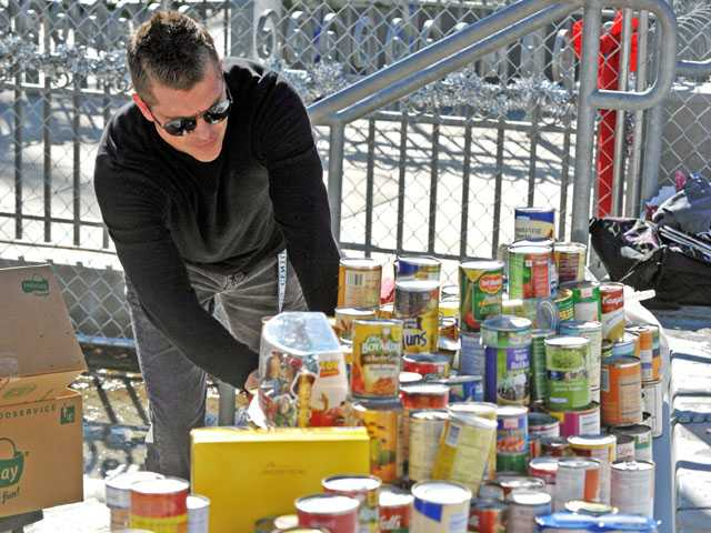 "Associated Student Body advisor Jeremy Fannon packs canned goods to be donated to the Santa Clarita Valley Food Pantry during Saugus High School's ""snow day"" on Monday. Students have been contributing to a food drive to benefit the food pantry since Dec. 1, Fannon said."
