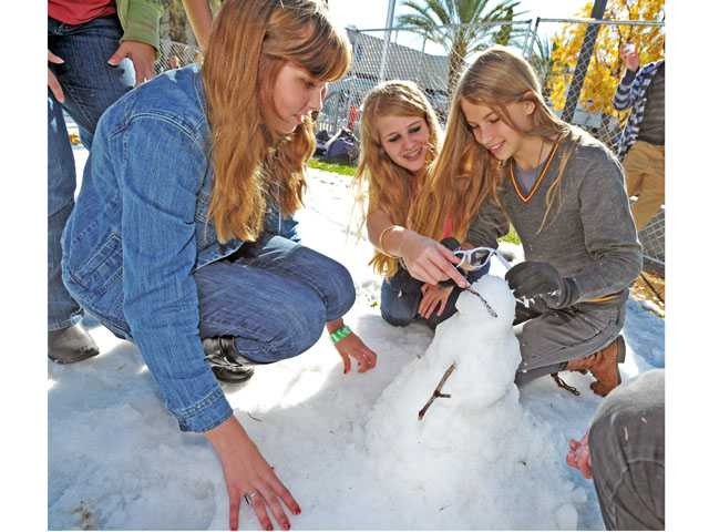 "From left, Anela Duxbury, Astoria Ryan and Jill Young fits sunglasses on Fabio ""the Hipster Snowman"" at Saugus High School's snow day on Monday."