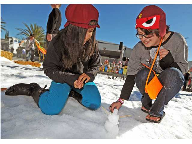 "Sabrina Barnes, left, and Monty Davis work on ""The Slender Snowman"" at Saugus High School's snow day on Monday."
