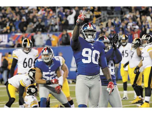 New York Giants defensive end and ex-College of the Canyons player Jason Pierre-Paul (90) reacts after the Giants defense stopped a fake field goal attempt by Pittsburgh Steelers during a game on Nov. 4 in East Rutherford, N.J.