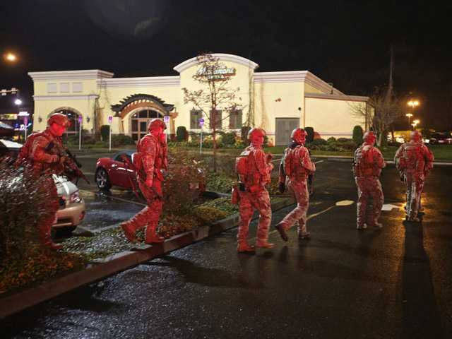 A tactical team moves through the mall parking lot at Clackamas Town Center in Portland, Ore., Tuesday.