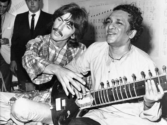 In this Aug. 3, 1967, photo, George Harrison, of the Beatles, left, sits cross-legged with his musical mentor, Ravi Shankar of India, in Los Angeles.