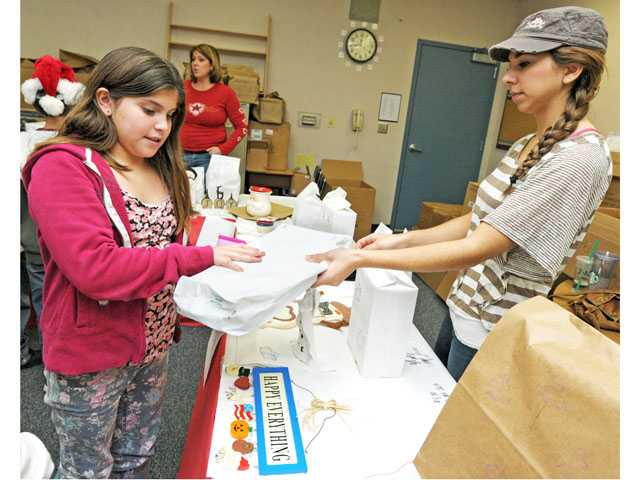 Fifth-grader Christiana Castro picks up a gift for her grandmother from Alicia Gonzales at Mitchell Community School's holiday boutique in Canyon Country on Tuesday.