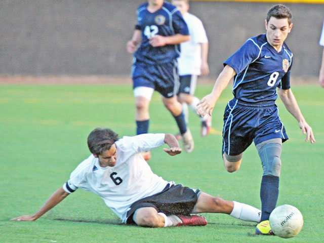 Trinity's Nick Spinello (8) dribbles past a skidding Christian Broadbent of Santa Clarita Christian on Tuesday at The Master's College.