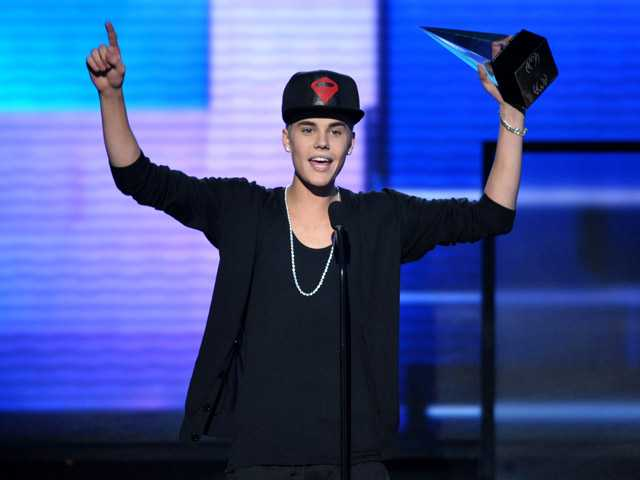 "In this Nov. 18 photo, Justin Bieber  accepts the award for favorite album - pop/rock for ""Believe"" at the 40th Anniversary American Music Awards, in Los Angeles."