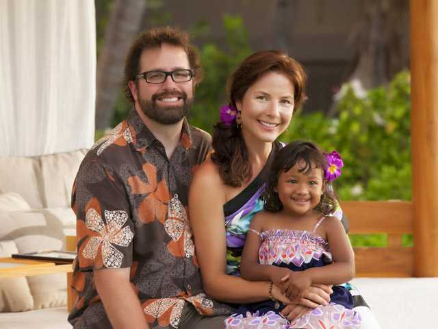 This May 2012 photo  shows, from left, Jed Taufer and Vicki Taufer of Morton, Ill., and their adopted 3-year-old daughter, Purnima, while the family was attending a wedding in Kona, Hawaii.