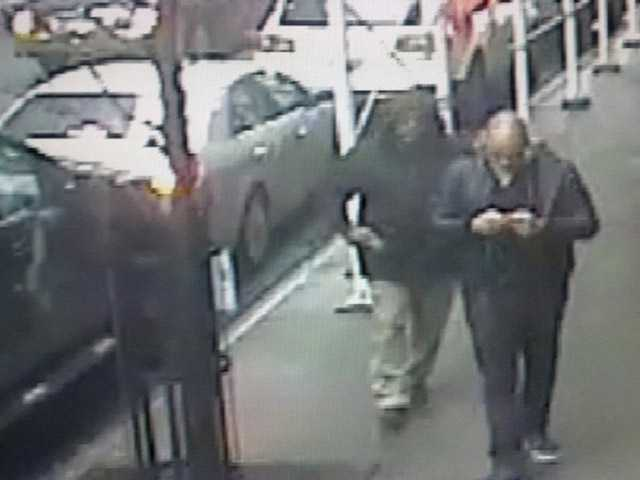 This still image shows the gunman, left, behind Brandon Lincoln Woodard  on Monday in New York.