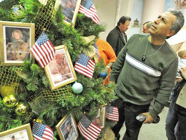 Bernie Sellen, a relative of Army Spc. Dennis L. Sellen Jr., looks at the Gold Star holiday tree during a reception for Gold Star families at Santa Clarita City Hall on Wednesday evening.