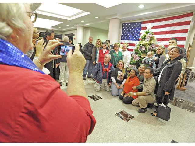 Sharon Ventrice, left, takes a photo of Gold Star family members alongside the Gold Star holiday tree at Santa Clarita City Hall on Wednesday evening.