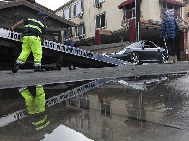 A Porsche sports car is towed away after flood waters damaged its electric systems near the overflowed streets onto Pacific Coast Highway in Sunset Beach on Thursday.