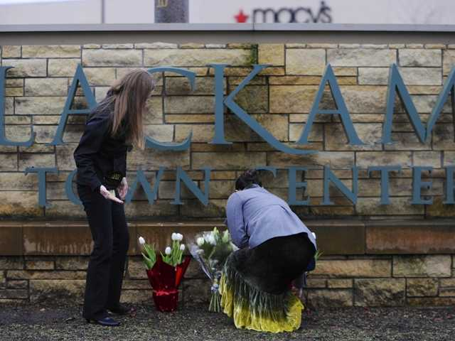 Leslie King, right and Tenille Beseda place flowers Wednesday  at the entrance to the scene of a multiple shooting yesterday at Clackamas Town Center Mall in Portland, Ore.